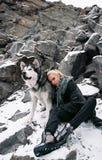 Muchacha con el Malamute del perro entre rocas en invierno Imágenes de archivo libres de regalías