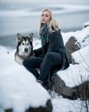 Muchacha con el Malamute del perro entre rocas en invierno Foto de archivo