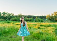 Muchacha con el manojo de manzanillas en un campo con la hierba alta Fotografía de archivo
