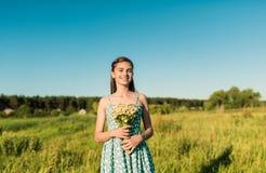 Muchacha con el manojo de manzanillas en un campo con la hierba alta Imágenes de archivo libres de regalías