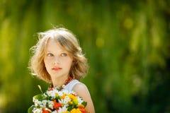 Muchacha con el manojo de wildflowers al aire libre Fotografía de archivo