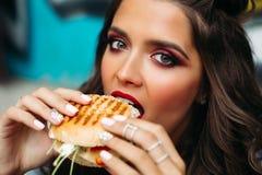 Muchacha con el maquillaje brillante que toma una mordedura de la hamburguesa Foto de archivo libre de regalías