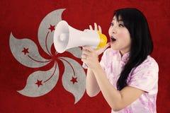 Muchacha con el megáfono y la bandera de Hong Kong Imágenes de archivo libres de regalías