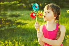 Muchacha con el molinillo de viento Foto de archivo libre de regalías