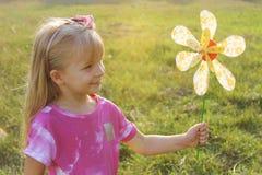 Muchacha con el molinillo de viento colorido en luz de la puesta del sol Fotografía de archivo libre de regalías