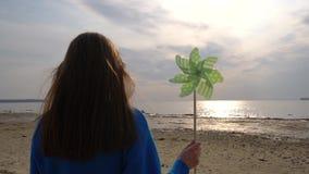 Muchacha con el molinillo de viento a disposición en la playa almacen de video