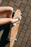 Muchacha con el monopatín de madera del longboard Foto de archivo