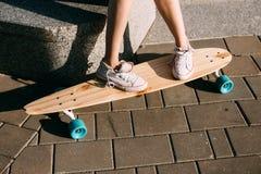Muchacha con el monopatín de madera del longboard Fotos de archivo