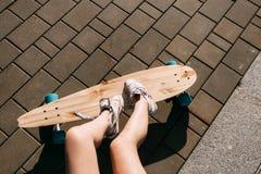 Muchacha con el monopatín de madera del longboard Imagen de archivo