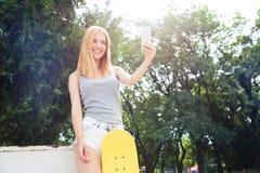Muchacha con el monopatín que hace la foto del selfie Imágenes de archivo libres de regalías