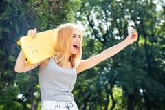 Muchacha con el monopatín que hace la foto del selfie en smartphon Imágenes de archivo libres de regalías