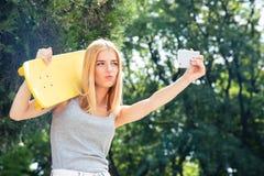 Muchacha con el monopatín que hace la foto del selfie en smartphone Imagen de archivo