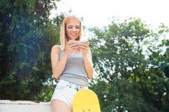 Muchacha con el monopatín usando smartphone Foto de archivo