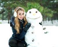 Muchacha con el muñeco de nieve Foto de archivo
