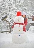 Muchacha con el muñeco de nieve Imagen de archivo