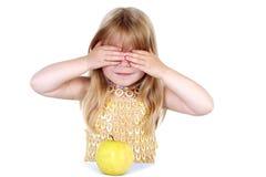 Muchacha con el ojo y la manzana de ocultación Imágenes de archivo libres de regalías