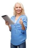 Muchacha con el ordenador de la PC de la tableta que muestra los pulgares para arriba Fotografía de archivo
