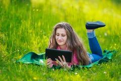 Muchacha con el ordenador de la tablilla Fotos de archivo