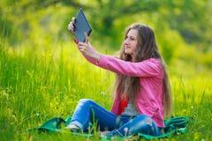 Muchacha con el ordenador de la tablilla Imágenes de archivo libres de regalías