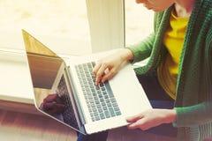 Muchacha con el ordenador portátil cerca de la ventana fotos de archivo