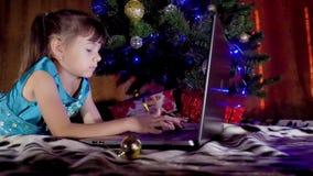 Muchacha con el ordenador portátil debajo del árbol de navidad En el Año Nuevo el niño está debajo de un árbol con un ordenador p almacen de metraje de vídeo