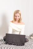 Muchacha con el ordenador portátil en cama Imagenes de archivo