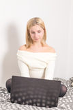 Muchacha con el ordenador portátil en cama Foto de archivo libre de regalías