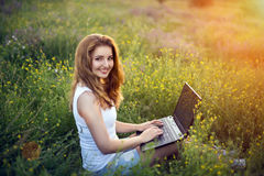 Muchacha con el ordenador portátil en campo Imágenes de archivo libres de regalías