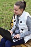 muchacha con el ordenador portátil en el parque Fotografía de archivo