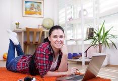 Muchacha con el ordenador portátil en el piso Fotografía de archivo