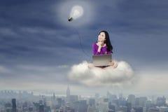 Muchacha con el ordenador portátil en la nube sobre ciudad Imagen de archivo libre de regalías