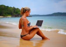 Muchacha con el ordenador portátil en la playa Fotografía de archivo