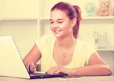 Muchacha con el ordenador portátil en la tabla Fotos de archivo