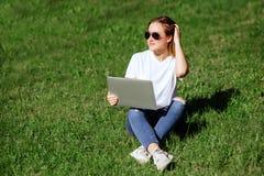 muchacha con el ordenador portátil en el parque imagenes de archivo
