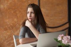 Muchacha con el ordenador portátil que mecanografía y que piensa Fotografía de archivo libre de regalías