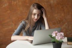 Muchacha con el ordenador portátil que mecanografía y que piensa Imagen de archivo