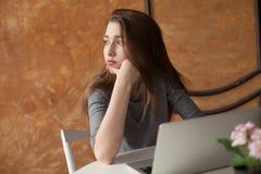 Muchacha con el ordenador portátil que mecanografía y que piensa Fotos de archivo
