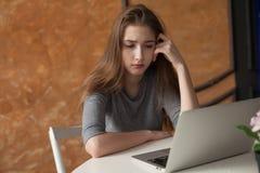 Muchacha con el ordenador portátil que mecanografía y que piensa Imágenes de archivo libres de regalías