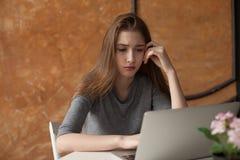 Muchacha con el ordenador portátil que mecanografía y que piensa Fotos de archivo libres de regalías