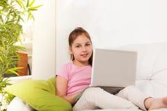 Muchacha con el ordenador portátil que se sienta en el sofá Imágenes de archivo libres de regalías