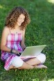 Muchacha con el ordenador portátil que se sienta en hierba Foto de archivo