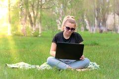 Muchacha con el ordenador portátil que se sienta en la hierba Fotos de archivo libres de regalías