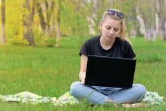 Muchacha con el ordenador portátil que se sienta en la hierba Imágenes de archivo libres de regalías