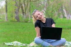Muchacha con el ordenador portátil que se sienta en la hierba Fotografía de archivo libre de regalías