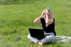 Muchacha con el ordenador portátil que se sienta en la hierba Foto de archivo