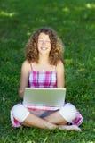 Muchacha con el ordenador portátil que se sienta en la hierba, ojos cerrados Fotos de archivo libres de regalías