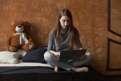 Muchacha con el ordenador portátil y el juguete Foto de archivo
