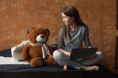 Muchacha con el ordenador portátil y el juguete Fotografía de archivo