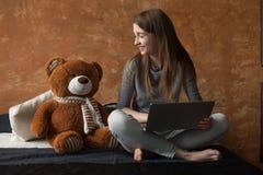 Muchacha con el ordenador portátil y el juguete Imagen de archivo libre de regalías