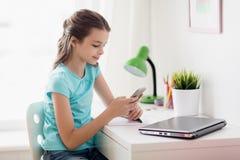 Muchacha con el ordenador portátil y smartphone que manda un SMS en casa Foto de archivo